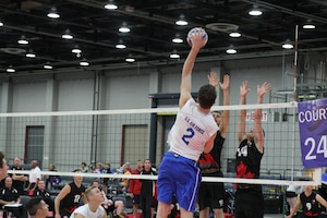 Air Force 2nd lt. Anthony Emtman of Dover AFB, Del. delivers a high spike over Team Canada during the 2015 Armed Forces Volleyball Championship held in conjunction with the USA Volleyball National Championship at the COBO Center in Detroit, Mich. 22-24.