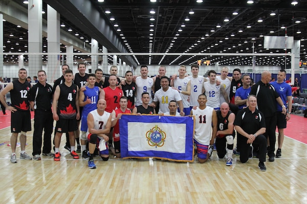 Service members from the Army, Navy and Air Force men's volleyball teams pose with Team Canada after a friendly international Conseil International du Sport Militaire (CISM) exhibition match during the 2015 Armed Forces Volleyball Championship held in conjunction with the USA Volleyball National Championship at the COBO Center in Detroit, Mich. 22-24.