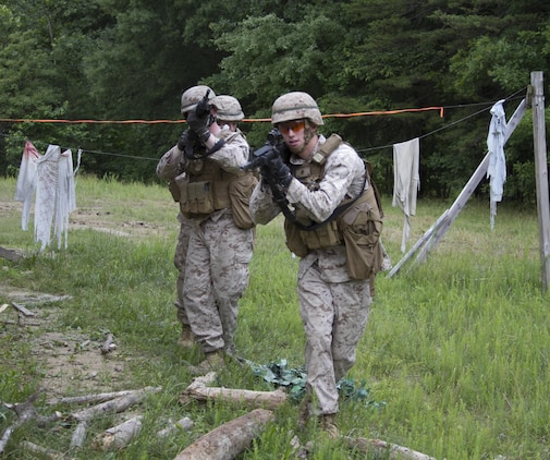 """Marines from Company B move toward an objective during training at Marine Corps Base Quantico's military operations in urban terrain, training facility. On June 17, 2015 more than 100 Marines from B Co., Marine Barracks Washington, D.C., traveled to the Quantico, Va. MOUT town to refine their individual actions in an urban environment. """"The training is focused on 1000-level training and readiness tasks [to include] making lower level entry into a compound and room clearing using proper techniques and procedures,"""" said Capt. David Moon, 3rd platoon commander, B. Co, Marine Barracks Washington, D.C. """"With the complexity of today's operating environment and the growth in large urban hubs this is the focus for the future. Although there is still importance on conventional warfare, a lot of the wars are fought in the urban environment."""" (U.S. Marine Corps photo by Cpl. Skye Davis/Released)"""