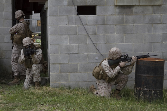 """Marines from Company B post security during training at Marine Corps Base Quantico's military operations in urban terrain, training facility. On June 17, 2015 more than 100 Marines from B Co., Marine Barracks Washington, D.C., traveled to the Quantico, Va. MOUT town to refine their individual actions in an urban environment. """"The training is focused on 1000-level training and readiness tasks [to include] making lower level entry into a compound and room clearing using proper techniques and procedures,"""" said Capt. David Moon, 3rd platoon commander, B. Co, Marine Barracks Washington, D.C. """"With the complexity of today's operating environment and the growth in large urban hubs this is the focus for the future. Although there is still importance on conventional warfare, a lot of the wars are fought in the urban environment."""" (U.S. Marine Corps photo by Cpl. Skye Davis/Released)"""