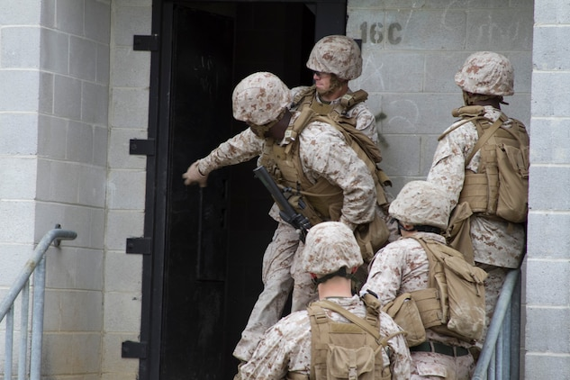 """A Marine from Company B throws a training grenade before entering a room during training at Marine Corps Base Quantico's military operations in urban terrain, training facility. On June 17, 2015 more than 100 Marines from B Co., Marine Barracks Washington, D.C., traveled to the Quantico, Va. MOUT town to refine their individual actions in an urban environment. """"The training is focused on 1000-level training and readiness tasks [to include] making lower level entry into a compound and room clearing using proper techniques and procedures,"""" said Capt. David Moon, 3rd platoon commander, B. Co, Marine Barracks Washington, D.C. """"With the complexity of today's operating environment and the growth in large urban hubs this is the focus for the future. Although there is still importance on conventional warfare, a lot of the wars are fought in the urban environment."""" (U.S. Marine Corps photo by Cpl. Skye Davis/Released)"""
