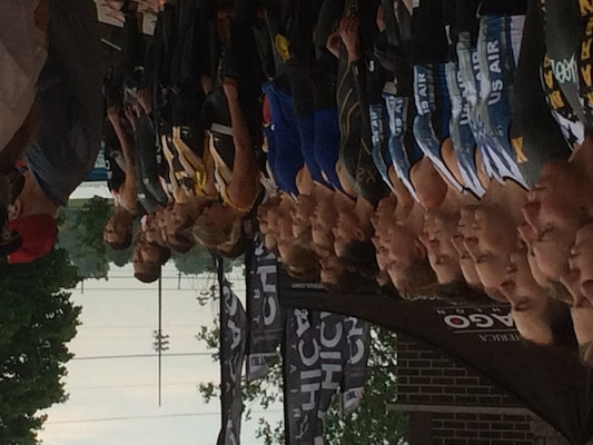 Service teams line up for the singing of the National Anthem during the 2015 Armed Forces Triathlon Championship held in conjunction with Leon's Triathlon in Hammond, Ind. on June 7.