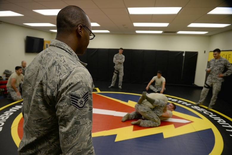 Staff Sgt. Felix Simon, 736th Security Forces Squadron Commando Warrior instructor, left, observes Airmen during a timed hand-to-hand combat exercise June 13, 2015, in the Pacific Regional Training Center at Northwest Field, Guam. Simon instructs security forces Airmen in essential combatives and tactical field skills. (U.S. Air Force photo by Senior Airman Alexander W. Riedel/Released)