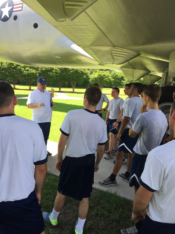 """As part of an """"Amazing Race"""" style event, 20 U.S Air Force Academy and Reserve Officers' Training Corps cadets visited Heritage Park June 15, 2015 at Joint Base Charleston, S.C., where Stan Gohl, the 437th Airlift Wing historian briefed the group on the history of the 437th AW and the three static jets that reside in the air park.  The cadets also visited Combat Arms Training and Maintenance where they handled weapons ranging from the M-9 pistol to a .50 Cal Sniper Rifle; Outdoor Recreation where they climbed a rock wall, challenging themselves to use team work to ensure everyone made it to the top. Lastly they ended the day with a friendly volleyball competition. During each stop, the Airman's Creed was incorporated into the visit and what the creed means to the enlisted personnel. The cadets are visiting JB Charleston as part of Operation Air Force, which exposes them to a real-world Air Force environment and provides them the opportunity to see how base components work together to meet the mission. This is the first of three groups scheduled to visit the base. (U.S. Air Force photo / Capt. Brian Walker)"""