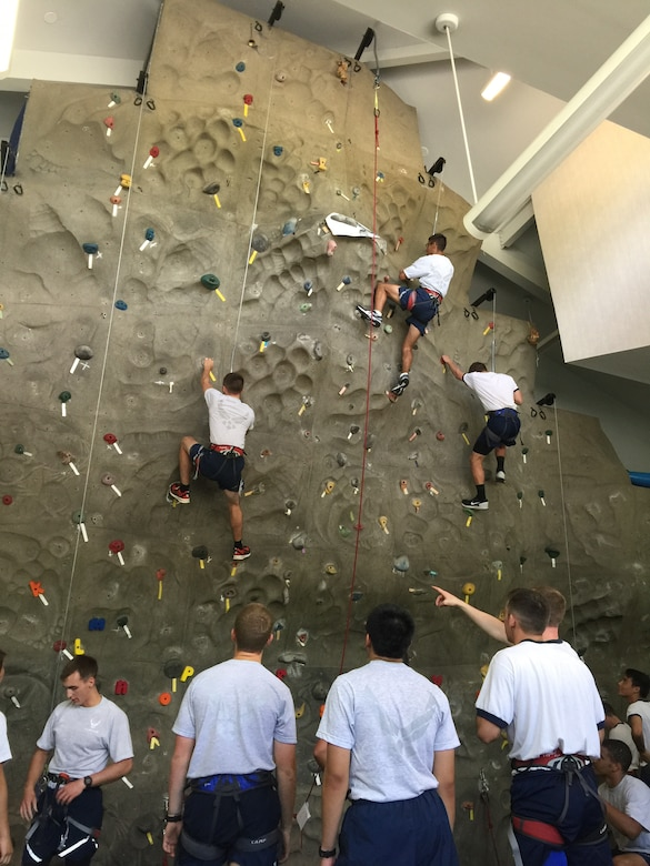 """As part of an """"Amazing Race"""" style event, 20 U.S. Air Force Academy and Reserve Officers' Training Corps cadets ran to Outdoor Recreation June 15, 2015 at Joint Base Charleston, S.C., where the cadets partnered up and took turns on the rock wall, challenging themselves and using teamwork to ensure everyone made it to the top. The cadets also visited the Heritage Park where Stan Gohl, the 437th Airlift Wing historian briefed the group on the history of the 437th AW and the three static jets that reside in the air park and Combat Arms Training and Maintenance where they handled weapons ranging from the M-9 pistol to a .50 Cal Sniper Rifle. During each stop, the Airman's Creed was incorporated into the visit and what the creed means to the enlisted personnel. The cadets are visiting JB Charleston as part of Operation Air Force, which exposes them to a real-world Air Force environment and provides them the opportunity to see how base components work together to meet the mission. This is the first of three groups scheduled to visit the base. (U.S. Air Force photo / Capt. Brian Walker)"""
