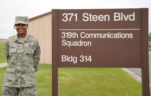 Tech. Sgt. Chenika Baker, 319th Communications Squadron NCO-in-charge, high frequency global communications system (HFGCS) bravo element, stands next to the 319th CS sign on Grand Forks Air Force Base, N.D., June 17, 2015. Baker was selected Warrior of the Week for the third week in June. (U.S. Air Force photo by Airman 1st Class Bonnie Grantham/Released)