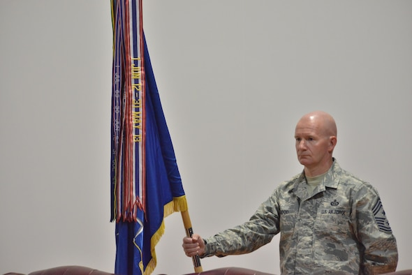 Chief Master Sgt. Thomas Good, 379th Air Expeditionary Wing command chief, holds the wing banner that will be used during the wing change of command June 14, 25015 Al Udeid Air Base, Qatar. Change of commands is a tradition that dates back to the Roman Legion in which authority is transferred from one commanding officer to another and is completed in front of the soldiers.  (U.S. Air Force photo/Staff Sgt. Alexandre Montes)