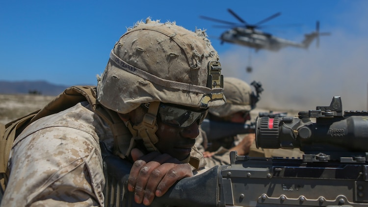 Corporal Kamen Pinkey, a motor transportation operator assigned to Company A, 1st Battalion, 11th Marine Regiment, 1st Marine Division, posts security for a CH-53E Super Stallion at Marine Corps Base Camp Pendleton, California, June 17, 2015. The CH-53s transported M777 howitzers and ammunition as part of 1/11's quarterly exercise to test the artillery Marines' proficiency and readiness.