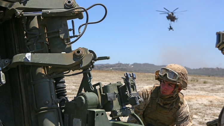A Marine assigned to Company A, 1st Battalion, 11th Marine Regiment, 1st Marine Division, prepares an M777 howitzer to fire at Marine Corps Base Camp Pendleton, California June 17, 2015. CH-53E Super Stallions transported howitzers and ammunition as part of 1/11's quarterly exercise to test the artillery Marine's proficiency and ensure the Marines' readiness.