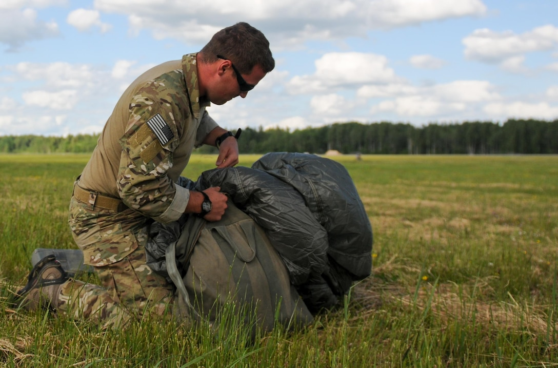 Senior Airman Jordan Thompson, a 169th Air Support Operations Squadron joint terminal attack controller, packs his parachute after jumping from a C-130 Hercules during the Baltic Jump Day event June 15, 2015, at Lielvarde Air Base, Latvia. More than 70 U.S. Air Force, U.S. Army and Latvian service members participated in a jump day to strengthen the bonds of allies and learn from each other during exercise Saber Strike 15. The exercise involved more than 6,000 service members from 14 nations and participation all throughout the Baltics to learn from each other and promote stability is the region. (U.S. Air Force photo/Capt. Chase P. McFarland)