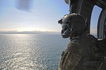 Senior Airmen Talon Leinbaugh, a 66th Rescue Squadron aerial gunner, conducts aerial surveillance in an HH-60G Pave Hawk over the Pacific Ocean during Angel Thunder 2015, June 11, 2015. Angel Thunder is hosted by the 355th Fighter Wing at Davis-Monthan Air Force Base, Ariz., but many flying operations extend throughout Arizona, New Mexico and California. Leinbaugh is stationed at Nellis Air Force Base, Nev. (U.S. Air Force photo/Senior Airman Betty R. Chevalier)