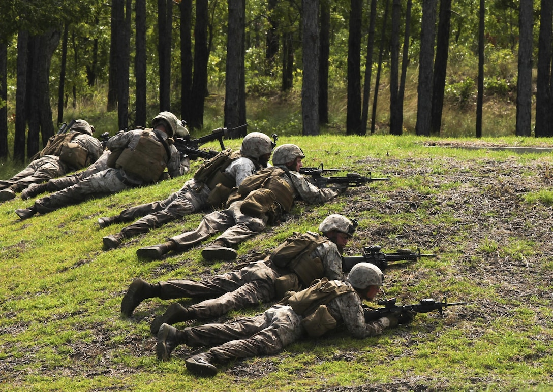 """Marines with Bravo Company, 2nd Combat Engineer Battalion, take a defensive position during a live-fire and maneuver exercise at a range aboard Camp Lejeune, N.C., June 6, 2015. The training simulated the Marine's response to encountering an enemy attack while on patrol. """"If we work together in this training we'll already know our plans, call signs and signals,"""" said Sgt. Christian Sampson, a combat engineer with the company. """"We'll have a plan laid out already so when we get in a fight we'll know what to do."""" (U.S. Marine Corps photo by Pfc. David N. Hersey/Released)"""