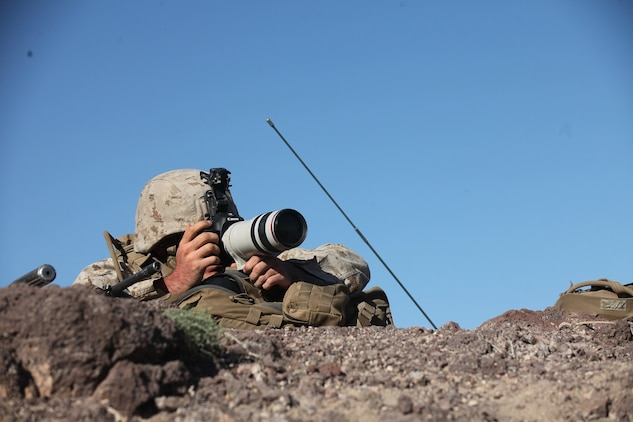 A forward observer with 1st Battalion, 7th Marine Regiment, 1st Marine Division, I Marine Expeditionary Force, photographs target positions for intelligence during 1/7's Marine Corps Combat Readiness Evaluation aboard Marine Corps Air Ground Combat Center Twentynine Palms, Calif., June 9, 2015. Marines from 1/7 and 2nd battalion, 7th Marine Regiment are currently in preparation for deployment with the Special Purpose Marine Air Ground Task Force (SPMAGTF) scheduled to depart in support of Operation Inherent Resolve later this year.