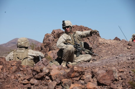 A sergeant with Company A, 1st Battalion, 7th Marine Regiment, 1st Marine Division, I Marine Expeditionary Force, directs his Marines into position atop a berm during 1/7's Marine Corps Combat Readiness Evaluation aboard Twentynine Palms, Calif., June 9, 2015.  Marines from 1/7 and 2nd battalion, 7th Marine Regiment are currently in preparation for deployment with the Special Purpose Marine Air Ground Task Force (SPMAGTF) scheduled to depart in support of Operation Inherent Resolve later this year.