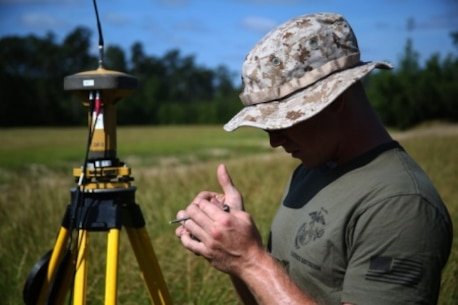 Private First Class Aaron Urbanski, a geographical intelligence specialist with Battlefield Surveillance Company, 2nd Intelligence Battalion, looks at data gathered by the base Global Positioning System during a geodetic survey of Landing Zone Lark aboard Camp Lejeune, North Carolina, May 28, 2015. Marines with the company are responsible for gathering information from each training area aboard Camp Lejeune, allowing pilots to determine whether the area is safe to land in or not.