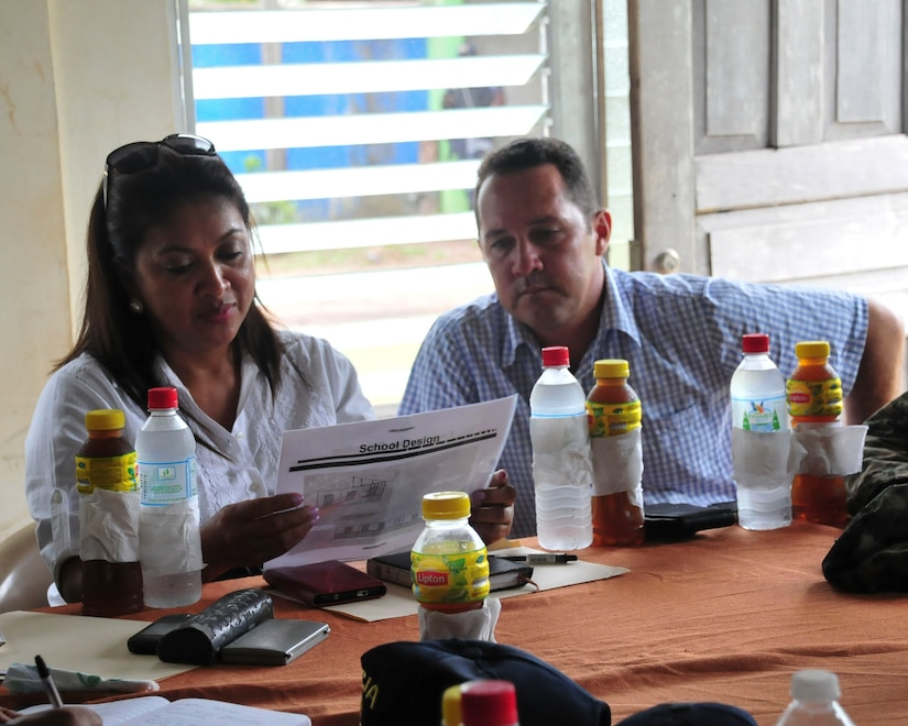 PUERTO LEMPIRA, Honduras – Marelin Bendles, the Ministry of Education representative for Gracias a Dios Department, and Alberto Haylock, the Governor of Gracias a Dios Department, review plans for a school to be built by the Special Purpose Marine Air Ground Task Force-Southern Command, during a bi-lateral meeting in Puerto Lempira, Honduras, June 18, 2015. The SPMAGTF-SC is based out of Soto Cano Air Base, Honduras, through November 2015 and plans to build two additional schools in Gracias a Dios, along with a road and airfield construction project. (U.S. Air Force Photo by Capt. Christopher Love)