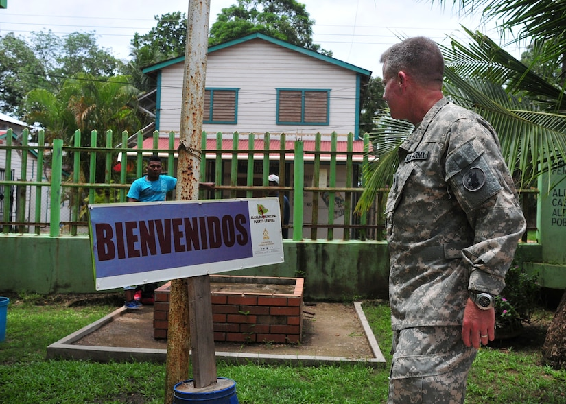 "PUERTO LEMPIRA, Honduras – U.S. Army Lt. Col. Daniel Moore, 1-228th Aviation Regiment commander, walks past a sign that says ""Welcome"" before entering a municipal building in Puerto Lempira, Honduras, June 18, 2015. Moore was part of a 14-member delegation from the Special Purpose Marine Air Ground Task Force-Southern Command and Joint Task Force-Bravo, both stationed at Soto Cano Air Base, Honduras, who met with Gracias a Dios department leaders to provide clarity on the Marines' upcoming constructions projects in the region. (U.S. Air Force Photo by Capt. Christopher Love)"
