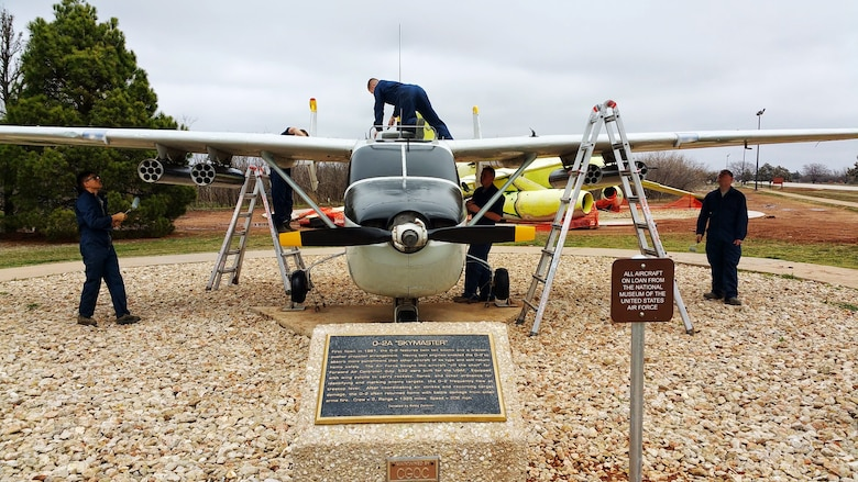 Dyess Airmen paint an O-2A Skymaster at the Linear Air Park March 10, 2015, at Dyess Air Force Base, Texas. More than 120 volunteers contributed more than 114,000 man hours over the course of seven weeks to complete a major restoration project of all 36 aircraft in the outdoor exhibit. (Courtesy photo)