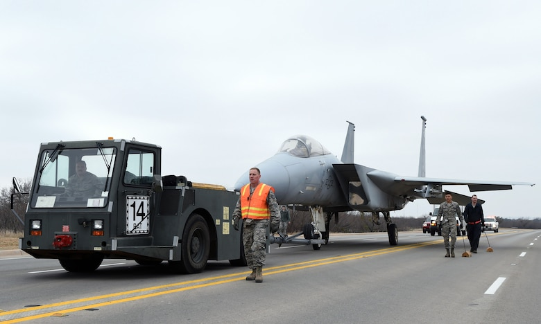 Dyess Airmen escort an F-15A Eagle to its new location Feb. 21, 2015, at Dyess Air Force Base. The F-15A is one of the new aircraft that was installed during a major project to improve and restore the Dyess Linear Air Park. (U.S. Air Force photo by Staff Sgt. Joel Mease/Released)