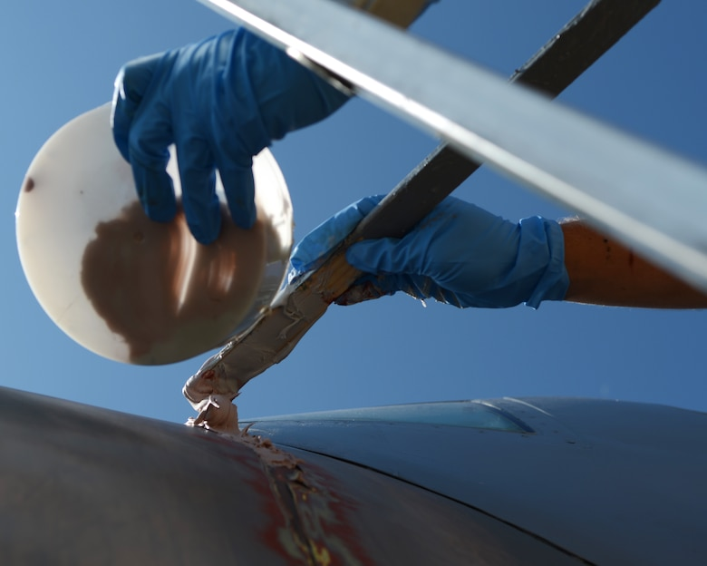U.S. Air Force Senior Airman Brandon Bartling, 7th Equipment Maintenance Squadron aircraft structural maintenance journeyman, applies body filler to a C-130E Hercules June 11, 2015, at Dyess Air Force Base, Texas.  More than 120 volunteers helped refurbish the Dyess Linear Air Park by repainting, bird-proofing, sanding, washing and repairing its 36 aircraft. (U.S. Air Force photo by Airman 1st Class Kedesha Pennant/Released)