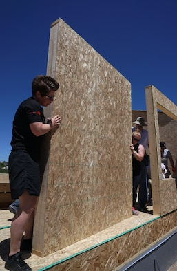 Senior Master Sgt. Jennifer Blackmarr, 90th Missile Wing Protocol Office, and Staff Sgt. Aubrie Jones, 90th Security Support Squadron, position a wall at the edge of the foundation during a Habitat for Humanity build June 14, 2015. Nine Airmen from F.E. Warren helped put up the frame of a house in Cheyenne, Wyo. (U.S. Air Force photo by Airman 1st Class Brandon Valle)