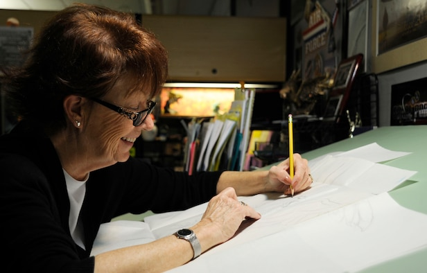 Jan Kays, 30th Space Wing visual information specialist, works on a griffin drawing in her office, June 11, 2015, Vandenberg Air Force Base, Calif. In the 15 years that Kays has worked in the graphics department at Vandenberg, she has had a profound impact on how the base is perceived by creating recognizable and aesthetically pleasing graphics. (U.S. Air Force photo by Airman 1st Class Ian Dudley/Released)