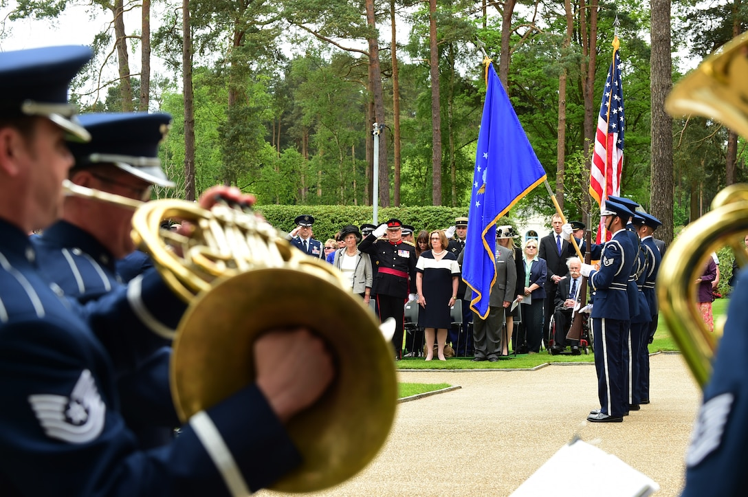 Airmen from the U.S. Air Forces Europe and Africa Band, play the American National Anthem as Airmen from the 422nd Air Base Group Honor Guard present the colors, during the Memorial Day ceremony at Brookwood American Military Cemetery, United Kingdom, May 24, 2015. The first American Service member burial was held May 1918, for members of the American Expeditionary Forces who lost their lives in Great Britain, the surrounding waters, from Influenza, and as a result of wounds suffered in France during World War I. (U.S. Air Force photo by Tech. Sgt. Chrissy Best/Released)