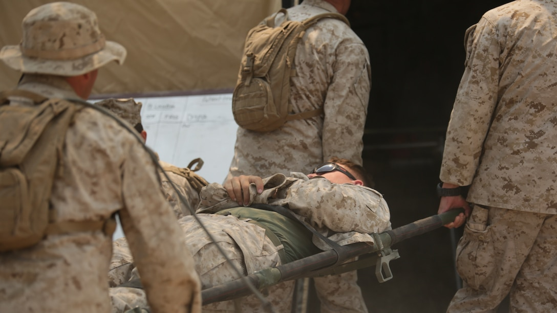 Marines with 4th Medical Battalion, 4th Marine Logistics Group, Marine Forces Reserve, carry a casualty in a mass heat casualty exercise during the 4-15 Integrated Training Exercise aboard Marine Corps Air Ground Combat Center, Calif., June 20, 2015. During the mass heat casualty exercise, Marines and sailors faced a situation where multiple casualties were rapidly brought into the medical station, and Marines and Sailors had to work together efficiently to ensure that all casualties were assessed and treated properly.