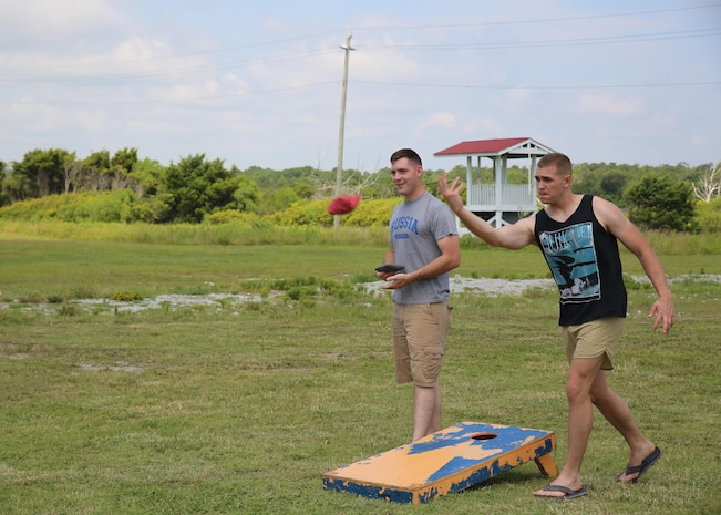 Sgt. Kevin Palmer, right, administrative specialist, Headquarters and Service Company, Ground Combat Element Integrated Task Force, tosses a bean bag during a game of corn hole at Onslow Beach aboard Marine Corps Base Camp Lejeune, North Carolina, June 19, 2015. From October 2014 to July 2015, the GCEITF conducted individual and collective level skills training in designated ground combat arms occupational specialties in order to facilitate the standards-based assessment of the physical performance of Marines in a simulated operating environment performing specific ground combat arms tasks. (U.S. Marine Corps photo by Cpl. Paul S. Martinez/Released)