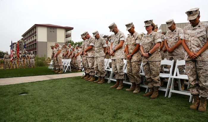 Service members of 1st Medical Battalion, 1st Marine Logistics Group, and distinguished guests, bow their head during the invocation at the 117th Hospital Corps Birthday ceremony aboard Camp Pendleton, Calif., June 17, 2015. The Hospital Corps came into existence as an organized unit of the medical department under the provision of an act of congress approved June 17, 1898. The hospital corpsmen work in a wide variety of capacities and locations, including shore establishments such as naval hospitals and clinics, aboard ships, and as the primary medical caregivers for Sailors and Marines while underway and forward deployed. (U.S. Marine Corps photo by Sgt. Laura Gauna/ Released)