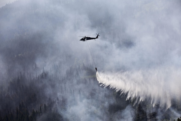 "An Alaska Army National Guard UH-60 Black Hawk from 1st Battalion, 207th Aviation Regiment, drops approximately 700 gallons of water from a ""Bambi Bucket"" on to the Stetson Creek Fire near Cooper Landing, Alaska, June 17, 2015. Two Black Hawks flew a total of 200 bucket missions, dumping more than 144,000 gallons of water on the 300-acre Stetson Creek Fire on the Kenai Peninsula. (U.S. Army National Guard photo/Sgt. Balinda O'Neal)"