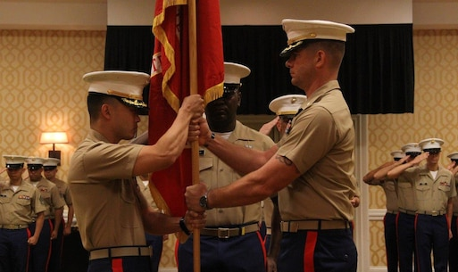 Major Richard Lee, incoming commanding officer of Recruiting Station Orlando, receives the Marine Corps Colors from Maj. Matthew Van Echo, outgoing commanding officer of Recruiting Station Orlando, during a change of command ceremony in Orlando, FL June 19, 2015. The passing of the colors symbolizes one commanding officer passing off the unit's mission and the Marines welfare onto another.