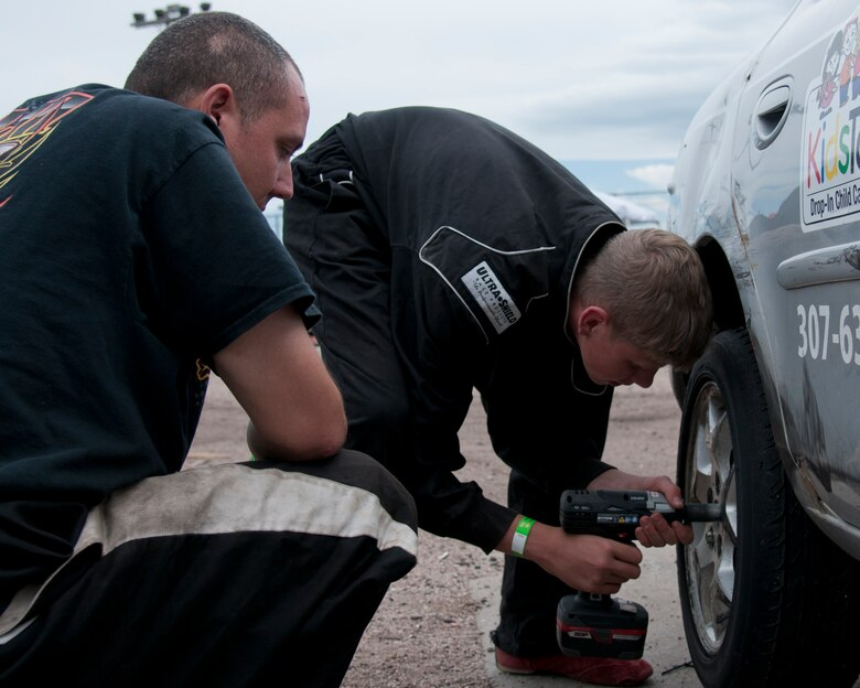 Maj. Neil Copenhaver, 20th Air Force deputy director of logistics, and his son, Jeron Schmidt, 13, replace a tire on Schmidt's stock car June 13, 2015, in Cheyenne, Wyo. Copenhaver is teaching Schmidt the ins and outs of stock car racing using the knowledge acquired from his time in racing leagues. (U.S. Air Force photo by Airman 1st Class Malcolm Mayfield)