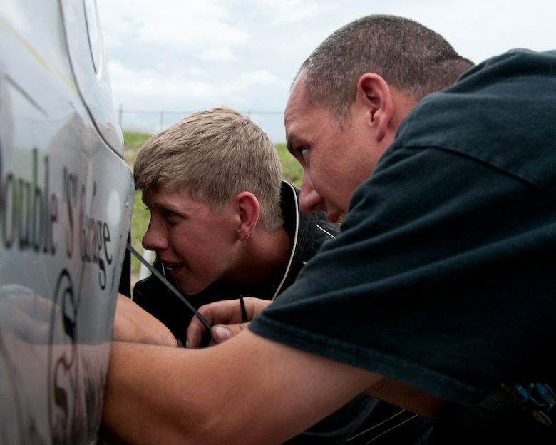 Maj. Neil Copenhaver, 20th Air Force deputy director of logistics, and his son, Jeron Schmidt, 13, finish their last inspection of Schmidt's stock car June 13, 2015, in Cheyenne, Wyo. This is Schmidt's first year of serious competitive racing. (U.S. Air Force photo by Airman 1st Class Malcolm Mayfield)