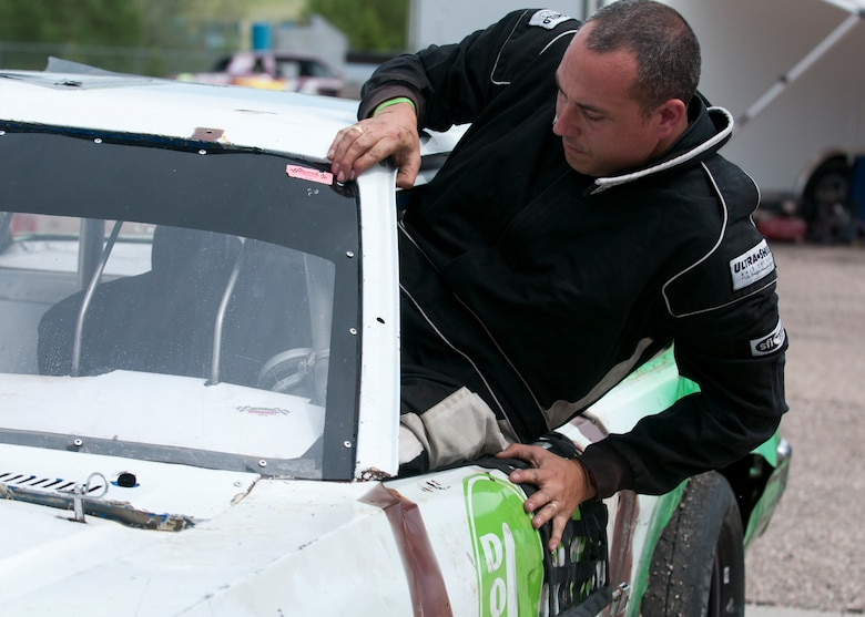 Maj. Neil Copenhaver, 20th Air Force deputy director of logistics, hops through the window into the driver's seat of his stock car June 13, 2015, in Cheyenne, Wyo. Copenhaver passed down his previous car to his son after winning last year's Warrior Class race with it. (U.S. Air Force photo by Airman 1st Class Malcolm Mayfield)