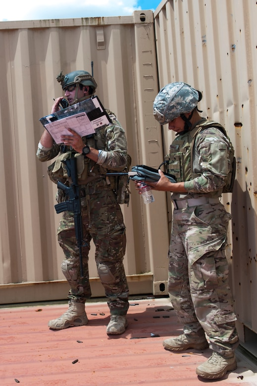 U.S. Air Force Staff Sgt. Robert Cooch, left, 18th Air Support Operations Group joint terminal attack controller, speaks with Staff Sgt. Rodshede Roberts, 820th Combat Operations Squadron technologies NCO, and A-10C Thunderbolt II pilots during Exercise DRAGON STRIKE June 9, 2015, at Avon Park Air Force Range, Fla. Roberts piloted an RQ-11B Raven, a small unmanned aerial vehicle, during the scenario to help Cooch locate simulated threats and describe their location to the A-10 pilots. (U.S. Air Force photo by Airman 1st Class Dillian Bamman/Released)