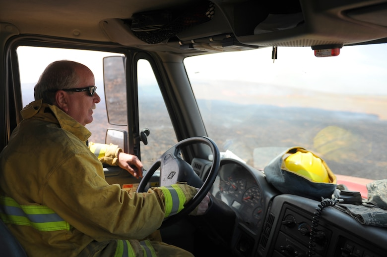 Mr. David Sunde, 9th Civil Engineer Squadron driver operator, drives a fire truck alongside a controlled burn at Beale Air Force Base, California on June 17, 2015. The burn consumed approximately 800 acres in an effort to renew cattle grazing land and control vegetation growth. (U.S. Air Force photo by Preston L. Cherry)