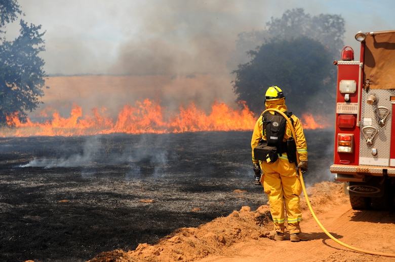 Airman 1st Class Joseph Crittenden, 9th Civil Engineer Squadron firefighter, monitors a controlled burn June 17, 2015 at Beale Air Force Base, California. The burn consumed approximately 800 acres in an effort to renew cattle grazing land and control vegetation growth. (U.S. Air Force photo by Preston L. Cherry)