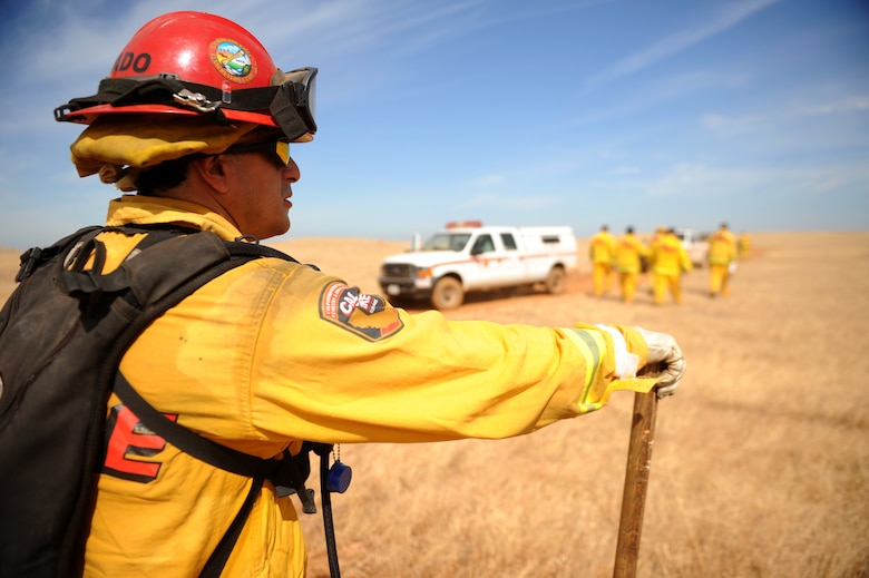Tony Dorado, CAL Fire Department fire captain B, scans the area during a controlled fire at Beale Air Force Base on June 17, 2015. The burn consumed approximately 800 acres in an effort to renew cattle grazing land and control vegetation growth. (U.S. Air Force photo by Preston L. Cherry)