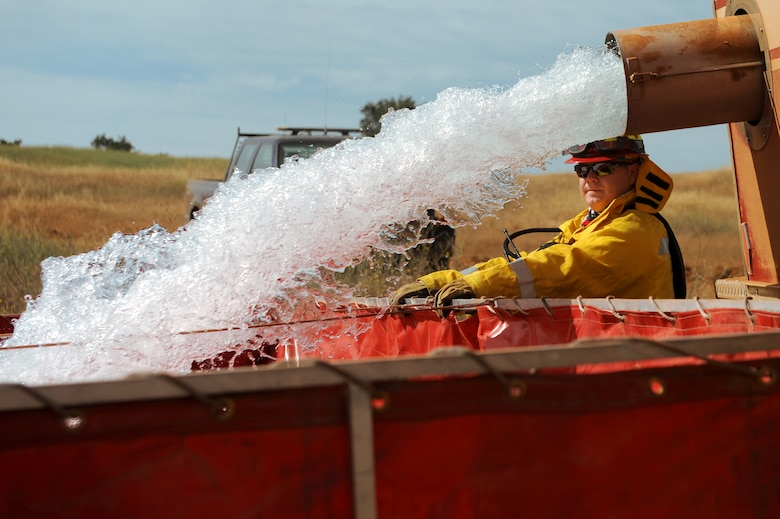 Staff Sgt. Vincent Kinard, 9th Civil Engineer Squadron firefighter, assists in filling a mobile water station for a controlled burn at Beale Air Force Base, California on June 17, 2015. The burn consumed approximately 800 acres in an effort to renew cattle grazing land and control vegetation growth. (U.S. Air Force photo by Preston L. Cherry)