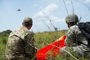 U.S. Air Force Staff Sgt. Ryan Hall, left, 18th Air Support Operations Group Survival, Escape, Resistance and Evasion specialist, helps Senior Airman Michael Cruz, 23d Operations Support Squadron targets intelligence specialist, signal an HH-60G Pave Hawk during a personnel recovery scenario for Exercise DRAGON STRIKE June 11, 2015, near Avon Park Air Force Range, Fla. Hall and Cruz utilized a VS-17 panel, a specialized signaling device, to highlight their location. (U.S. Air Force photo by Airman 1st Class Dillian Bamman/Released)