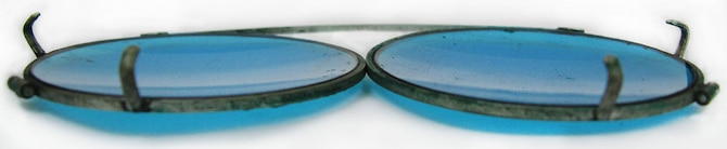 These blue-tinted clip-on sunglasses were worn by 1st Lt. Carroll DeWitt McClung with his prescription eyeglasses. They are approximately 3-3/8 - 4 inches in width and were manufactured to stretch to fit and clip onto various size prescription eyeglass frames. This style of clip-on sunglasses is still manufactured and used today. (U.S. Air Force photo)