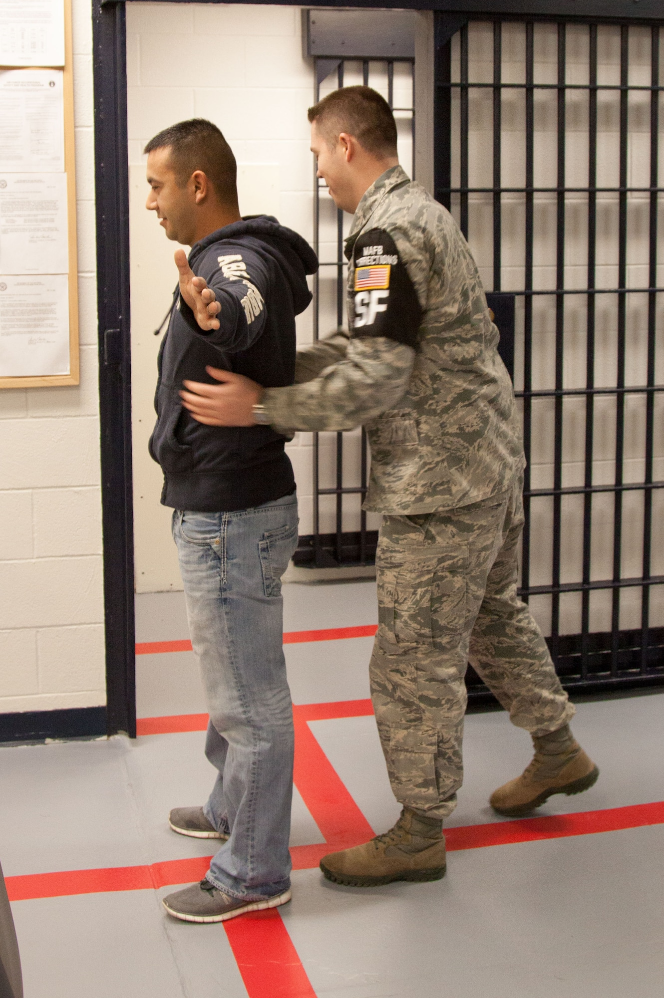Staff Sgt. Jaime Gutierrez, a 341st Security Forces Support Squadron trainer (left), simulates an inmate during inprocessing as Tech. Sgt. Earl Bagwell, the 341st Security Forces Squadron NCO in charge of investigations, pats him down at Malmstrom Air Force Base's confinement center. Reoccurring training sessions for confinement supervisors provide the skills necessary for them to complete their mission safely and efficiently. (Courtesy photo)