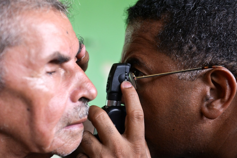 Dr. Miguel Coello, a Joint Task Force – Bravo Medical Element medical liaison officer, performs an eye exam on a patient during a medical readiness training exercise, June 2, 2015, at Corinto, Cortes, Honduras. Coello participates in 12-15 MEDRETEs each year in under-reached portions of Honduras and Central America. (U.S. Air Force photo by Staff Sgt. Jessica Condit)