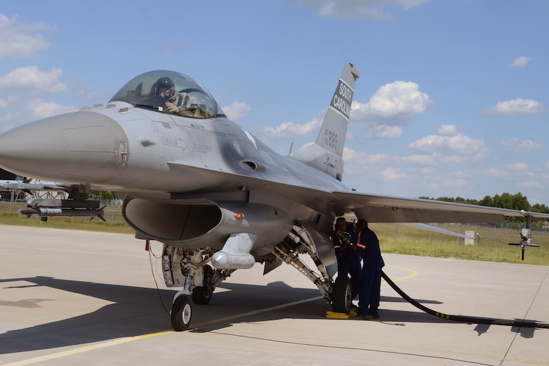 """Polish air force Young Warrant Officer Adam Maksymowicz and Senior Sgt. Pawel Czapski, both from the 32nd Tactical Air Base at Łask Air Base, Poland, """"hot-pit"""" refuel a South Carolina Air National Guard F-16 fighter jet, piloted by Capt. Mark """"Dirty"""" Fattman, June 1, 2015. F-16 aircraft maintenance crews from the Polish 32nd Tactical Air Base and the South Carolina Air National Guard's 169th Fighter Wing teamed-up to conduct """"hot-pit"""" refueling at Łask Air Base, Poland, June 1, 2015. The 32nd Tactical Air Base was recently certified to perform """"hot-pit"""" refueling, which involves refueling a recently landed F-16 so that it can take off for another mission without stopping its engine. Three units worked together to learn """"hot-pitting"""" techniques from each other as well as offering opportunities for Polish Airmen to learn from the more seasoned 169th Fighter Wing and 52d Fighter Wing maintainers. U.S. Air Force Airmen from Spangdahlem Air Base, Germany and the South Carolina Air National Guard's 169th Fighter Wing from McEntire Joint National Guard Base, are deployed to Łask Air Base in support of Operation Atlantic Resolve, during the month of June. These training missions, called Aviation Detachment Rotations, pair U.S. fighter pilots and maintenance crews with their Polish Air Force counterparts at Łask Air Base, during Operation Atlantic Resolve. This bilateral training, hosted by permanently assigned USAF service members assigned to Poland, has taken place since 2012. Through strengthened relationships and engagements with our allies, the U.S. and NATO demonstrate their shared commitment to a peaceful, stable and secure Europe. (South Carolina Air National Guard photo by Senior Master Sgt. Edward Snyder / RELEASED)"""