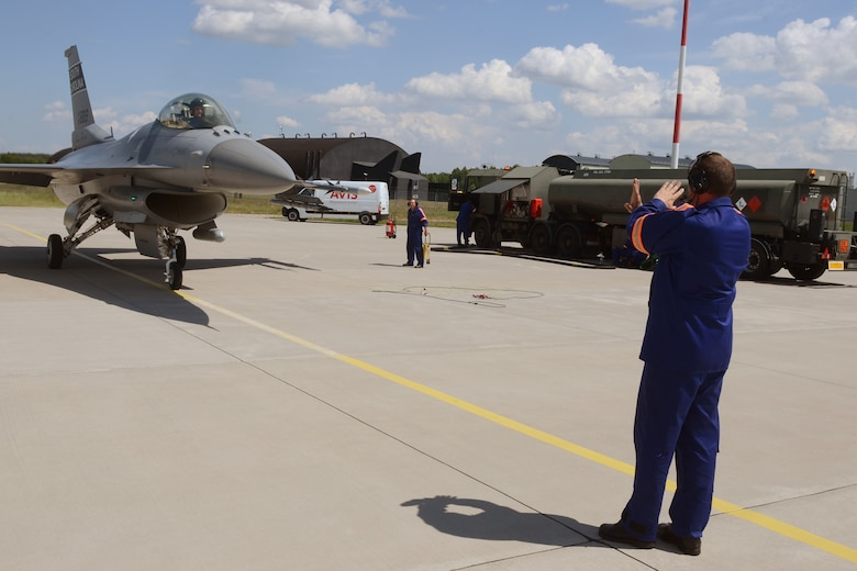 """Polish air force Warrant Officer Witold Bukowiec, from the 32nd Tactical Air Base at Łask Air Base, Poland, marshals a South Carolina Air National Guard F-16 fighter jet, piloted by Capt. Mark """"Dirty"""" Fattman, to be """"hot-pit"""" refueled, June 1, 2015. F-16 aircraft maintenance crews from the Polish 32nd Tactical Air Base and the South Carolina Air National Guard's 169th Fighter Wing teamed-up to conduct """"hot-pit"""" refueling at Łask Air Base, Poland, June 1, 2015. The 32nd Tactical Air Base was recently certified to perform """"hot-pit"""" refueling, which involves refueling a recently landed F-16 so that it can take off for another mission without stopping its engine. Three units worked together to learn """"hot-pitting"""" techniques from each other as well as offering opportunities for Polish Airmen to learn from the more seasoned 169th Fighter Wing and 52d Fighter Wing maintainers. U.S. Air Force Airmen from Spangdahlem Air Base, Germany and the South Carolina Air National Guard's 169th Fighter Wing from McEntire Joint National Guard Base, are deployed to Łask Air Base in support of Operation Atlantic Resolve, during the month of June. These training missions, called Aviation Detachment Rotations, pair U.S. fighter pilots and maintenance crews with their Polish Air Force counterparts at Łask Air Base, during Operation Atlantic Resolve. This bilateral training, hosted by permanently assigned USAF service members assigned to Poland, has taken place since 2012. Through strengthened relationships and engagements with our allies, the U.S. and NATO demonstrate their shared commitment to a peaceful, stable and secure Europe. (South Carolina Air National Guard photo by Senior Master Sgt. Edward Snyder / RELEASED)"""