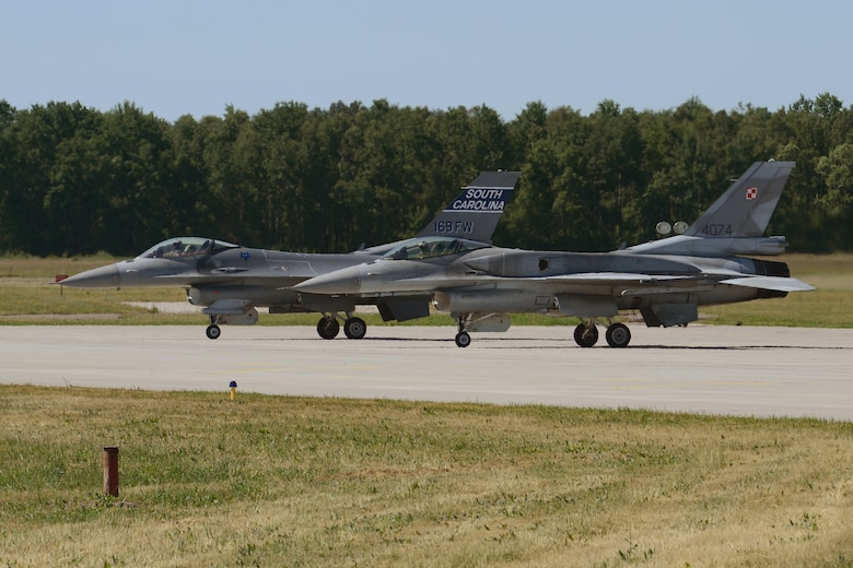 F-16 fighter jets from Poland's 32nd Tactical Air Base and the South Carolina Air National Guard prepare to taxi for takeoff at Łask Air Base, Poland in support of Operation Atlantic Resolve, June 5, 2015. U.S. Air Force Airmen from Spangdahlem Air Base, Germany, and the South Carolina Air National Guard's 169th Fighter Wing from McEntire Joint National Guard Base, are deployed to Łask Air Base in support of Operation Atlantic Resolve, during the month of June. These training missions, called aviation detachment rotations, pair U.S. fighter pilots and maintenance crews with their Polish air force counterparts at Łask Air Base, during Operation Atlantic Resolve. This rotation, AvDet 15-3, is the first to combine guard/reserve and active-duty units in Poland to offer more diverse opportunities to share best practices and build professional relationships with the Polish air force. This bilateral training, hosted by permanently assigned USAF service members assigned to Poland, has taken place since 2012. Through strengthened relationships and engagements with our allies, the U.S. and NATO demonstrate their shared commitment to a peaceful, stable and secure Europe. (South Carolina Air National Guard photo by Senior Master Sgt. Edward Snyder / RELEASED)