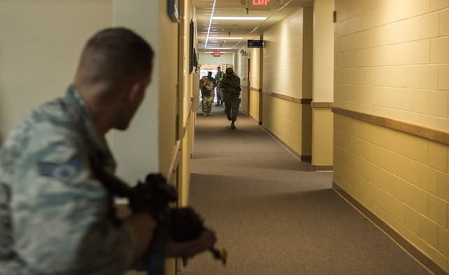 "Senior Airman Kyle Honeycutt, role-playing an active shooter, stares down the hall as Security Forces members race towards him during the exercise June 18, 2015, at Mountain Home Air Force Base, Idaho. A call was made to Security Forces moments after the first ""shots"" were fired. (U.S. Air Force photo by Airman 1st Class Jeremy L. Mosier/RELEASED)"
