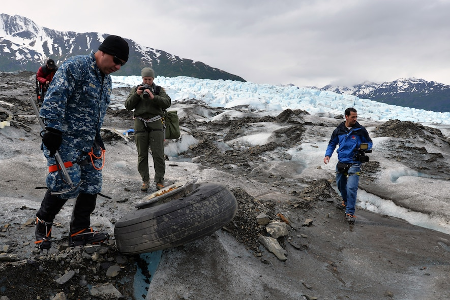 Navy Lt. Commander Paul Cocker (left), Alaskan Command deputy chief of future operations and Operation Colony Glacier project officer, shows local media some of the aircraft debris from the 1952 C-124 Globemaster II aircraft accident June 10. Each summer since 2012 Alaskan Command has supported Operation Colony Glacier by removing aircraft debris and assisting in the recovery of human remains to ensure closure for families who have lost loved ones.  (U.S. Air Force photo/Tech. Sgt. John Gordinier)