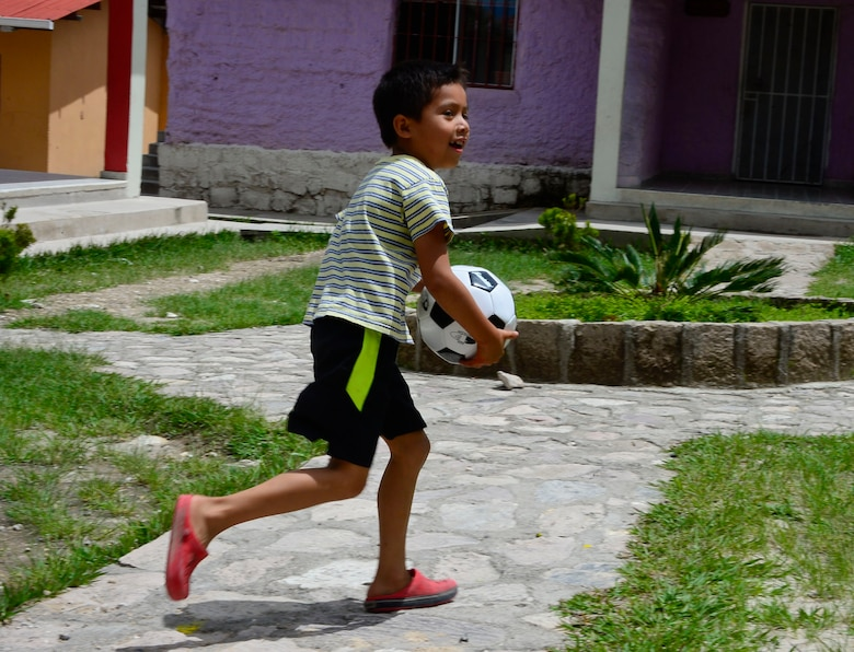 A young boy from the Casa de Corderitos orphanage in Tegucigalpa, Honduras plays with his new soccer ball, June 18, 2015. The 12th AF (AFSOUTH) members spent some of their downtime during a three-day assessment visit to Honduras Air Bases to volunteer with the local community and to deliver toys and candy that were donated by businesses in Tucson, Ariz. (U.S. Air Force photo by Tech. Sgt. Heather R. Redman/Released)